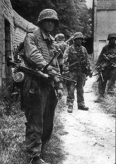https://flic.kr/p/993c3q | SS-Schütze Klaus Schuh (KIA 26.06.1944) and SS-Unterscharführer Koslowski, of SS-Panzergrenadier Regiment 25, 12. SS-Panzerdivision 'Hitlerjugend' after the fierce fightings in Norrey-en-Bessin. Rots, northwest at Caen, Normandy. 9 June 1944.