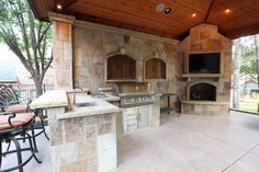 Large, open outdoor kitchen featuring BBQ, ice chest, sink and fireplace. By Outdoor Signature in Argyle, TX