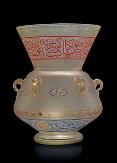 "AN ENAMELLED GLASS MOSQUE LAMP IN THE NAME OF 'ABBAS HELMI PASHA  EGYPT, DATED AH 1328/1910 AD  Of typical Mamluk form with sloping rounded body and flared mouth on short foot, six simple loop handles around the body, the surface decorated in red and blue enamels and gilt with a band of blue outlined red thuluth around the mouth, the underside of the body with similar calligraphy in blue outlined with gold and divided by two roundels giving the name of the patron as 'Abbas Helmi...13 1/8""…"