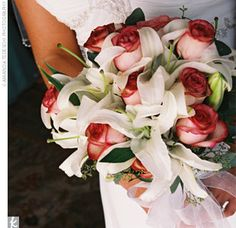 hand-tied bouquet overflowed with white calla lilies and Rossini roses in a crescent shape that was tied off with a sheer, ivory ribbon.
