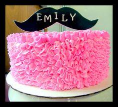 <b>Pink</b> ruffle <b>cake</b> with <b>mustache</b> on top.