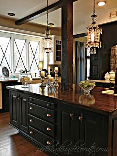 The color palette in this gorgeous kitchen makeover is so deliciously dramatic! The black cabinets are painted with Behr Ultra in black. All the white you see is Behr Swiss Coffee. Click through to see more of glam kitchen on Redhead Can Decorate. || @mamamioni