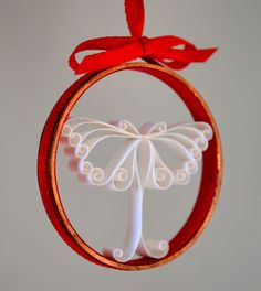 """A moth Christmas ornament. It's made of curled (or """"quilled"""") strips of white paper in a copper ring lined with red paper and tied round with red ribbon."""