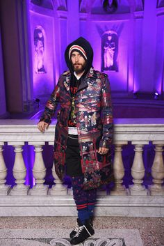 Jared Leto in a silk jacquard coat, embroidered hooded sweatshirt, technical jersey shorts, jacquard knit pants and high-top sneakers.