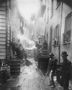 Jacob Riis' most famous photograph of Bandits Roost. Gang members stare menacingly at the camera. By the stairwell is a stale beer hall.