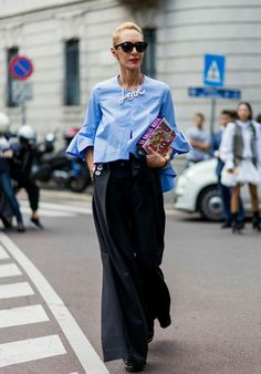 Love this street style look! What gorgeous and sophisticated style ideas and inspiration.Wide leg trousers with button detailing, beautiful blue shirt with frill sleeve and the statement 'Love' necklace - so chic.