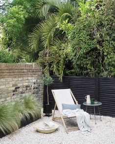 Green urban oasis - black painted fencing - white gravel - green home - urban garden