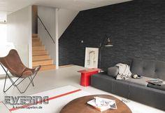 Rasch Factory 05 - Eine Vliestapete mit Stein-Mauer in schwarz wirkt elegant im Wohnzimmer.
