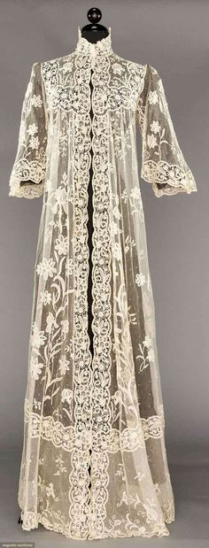 """BRUSSELS LACE PEIGNOIR, 1905 White cotton tulle w/ floral appliques of iris, lillies-of-the-valley, etc., edging & insertions of Brussels lace guipure, bell sleeves & trained, B 34"""", L 63""""-80"""", excellent."""