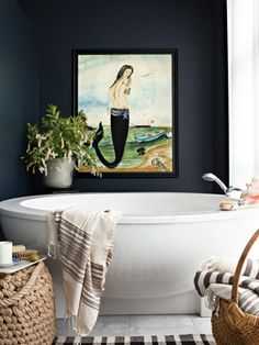 Country Living - In this Pennsylvania house, an extra-large Hoesch bathtub pops against walls painted in Behr's Sled, as does an original mermaid painted by Pennsylvania artist Kolene Spicher. A basket of towels, as well as a bathside candle, help bring a snug feeling to the room.