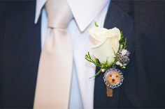 Winter white rose boutonniere from 2015 Winter wedding at Lakeview Pavilion featured in January 2017 Southern New England Weddings Magazine | Flowers by Judy's Village Flowers | Photos by Sabrina Scolari Photography