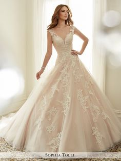 Sophia Tolli Y11705 Estelle - Misty tulle ball gown with illusion slight cap sleeves adorned in generously hand-beaded lace appliqués and scattered beading, deep V-neckline with partially concealed sheer peekaboo, lightly beaded lace appliqués adorn bodice and spill down voluminously folded skirt, back corset, chapel length train.