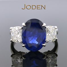 This ring is admired by all who see it's rich blue sapphire and bright diamonds that beautifully highlight the classic design. All the focus is centered on the oval cut sapphire with a weight of 5.24 carats. With a color of blue and very lightly included this sapphire really shows it's beauty. Flanked by two bright cushion cut diamonds graded by the Gemological Institute of America.