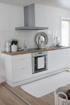 #13. Tiny white contemporary kitchen with wooden countertop, no upper cabinets, white rug, solid wood floors, white tile splash back.