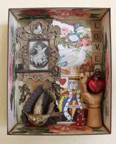 This is a mixed media assemblage that is within a vintage chocolate tin. The tin is 7 X 8.5 and it is 2 1/4 deep.The sides are embellished with