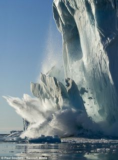 Meling away: A slab of ice falls from an iceberg in Disko Bay on a sunny summer evening in Ilulissat, Greenland.