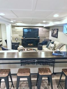 A narrow counter height bar behind a sectional in a rustic chic basement remodel. We added interest and added heat with a fireplace tv console from Raymour & Flanigan.