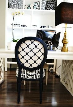 COCOCOZY HQ office space with a vintage brass Stiffel lamp and white orchid sitting on a White Laquer Fertwork Parsons Desk, navy Louis chai...