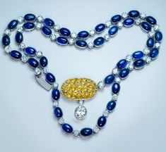 A Vintage Sapphire Diamond Platinum Necklace, circa 1930s. The necklace is bezel-set with 39 cabochon cut blue sapphires and 40 old European and transitional cut diamonds. The oval clasp with two-stone diamond pendant is densely set with round faceted yellow sapphires.