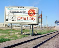 Billboard advertising Liberace at The Sun Bowl in Sun City along Grand Avenue in the At left is Eller Outdoor, at right is the Goodyear sign Sun City, Billboard, Railroad Tracks, 1960s, Advertising, Signs, Retirement, Outdoor, Shape