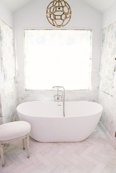 Bathroom with white walls, white tile floors, white bathtub, and light brown rope light fixture