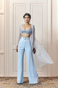 Powder blue crop top with thread, silver poth (small beads), sequin, and silver salli (pipes) embroidery on net paired with georgette pants with a belt and an organza cape Indian Fashion Dresses, Indian Gowns Dresses, Dress Indian Style, Indian Designer Outfits, Fashion Outfits, Stylish Dress Designs, Stylish Dresses, Stylish Outfits, Modern Blouse Designs