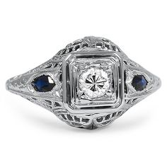 The Vesna Ring from Brilliant Earth circa 1930's An exquisite round brilliant diamond is nestled within a double square frame and is highlighted on either side by a splendid, rich blue French cut sapphire. The Edwardian-era piece is enhanced by gorgeous detailing in the precious metal, including fine milgrain and a luxurious open net motif on both sides of the gallery (approx. 0.20 total carat weight)