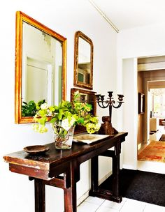Tour a Feminine, Collected Barcelona Home // Rustic Entryway With Wooden Mirrors and a Consol