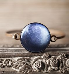 navy blue bracelet with a round cabochon inspired by planet Pluto.