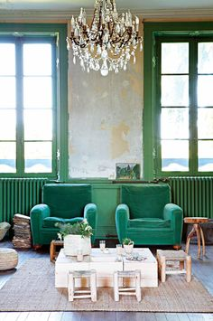Green chairs and window frames in a 12th-century French chateau turned into bohemian family home