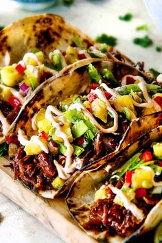 These Pulled Pork Tacos are a symphony of exotic and spectacular Asian flavor and texture in each can't stop eating bite! They are stuffed with juicy, tender Asian Caramel Pulled Pork and piled with fresh and tangy Pineapple Snow Pea Salsa and drizzled with luxurious Sriracha Crema.