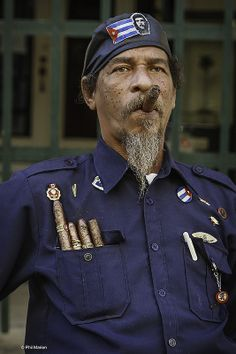 Pinner wrote: 'Cigar chomping resident of Havana, Cuba' ---BUT - actually it's more like 'Communist sympathizer and soldier chomping on cigars in Castro's NEW Cuba'
