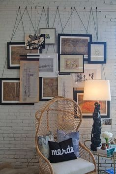 idea: attach rope/cord to frames, and hang from what looks like a series of small hooks on a painted 2x4. alternately: hang from a curtain rod so frames can be rearranged more easily. Nadia Geller's Downtown Design Studio Workspace Tour