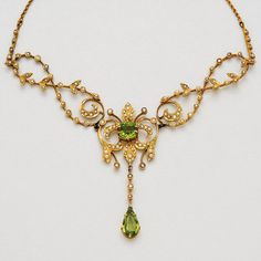 Peridot, Split-Pearl and Gold Necklace   The antique pendant of scroll and foliate motifs, set with split pearls and a pair of peridots together weighing approximately 4.15 carats, mounted in 14k, and joined to a 10k gold ropetwist linking chain, length 20 1/2 ins