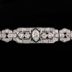 Featured here is an incredible original vintage diamond and emerald bracelet from the Art Deco period! This is a show stopping piece with over 4.5 carats of sparkling high quality diamonds and over 19 grams of solid platinum! These diamonds are F-G VS and is testament that the original maker only used top quality materials. It is truly impressive and it is one of our favorite items in our shop. It must be seen in person to be fully appreciated. The center stone is a 0.75ct marquise diamond…