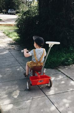 So cute sunny day play outfit. Baby boy street style overall outfit with mustard salopette. Adjustable straps means it grows with babe, and elastic waist with super soft organic cotton means his sensitive skin stays safe and sound. riding little red tricycle, boho baby chic.