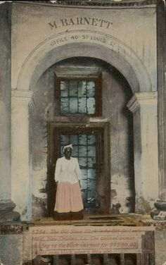 """Early 20th century photo postcard showing a dilapidated slave block at what had been the biggest slave market in the South, at the Old St. Louis Hotel in New Orleans  The woman in the photo, according to the caption, """"was sold for $1500.00 on this same block when a little girl."""" (Public domain via Wikimedia Commons.)"""