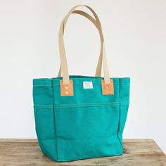 No. 103 Carry Tote in bottle green duck canvas with Horween leather. Handmade in Omaha, Nebraska. Lifetime guarantee.