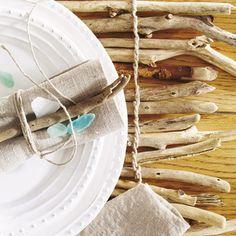 Aus Treibholz lässt sich eine tolle Tischdeko basteln.    So geht's:    - Die Äste werden - parallel gelegt und mit Paketschnur verknotet - zum Tischset.  - Für die Tellerdeko einen Ast auf die Serviette legen und mit Paketschnur umwickeln.   - Auf dem Teller platzieren und mit Seeglas dekorieren.
