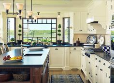 White cabinets with dark wood and dark counters. What really takes the cake in this kitchen are the giant windows above the sink.