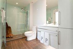 Frameless shower doors, mosaic tile shower floors, Lustrolite panels and Sasha Alexandra vanity.