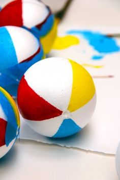 Pool Party Beach Ball Garland DIY - smooth foam balls, taped off with painters tape, paint with craft paint, attach to string with a spot of hot glue