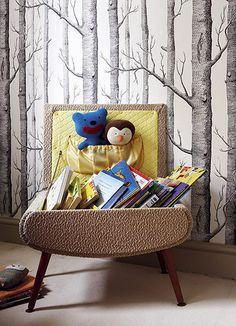 A sewing box picked up at a car boot sale is perfect for housing children's books. And think beyond kiddie wallpaper designs: this boy's room is papered with a black-and-white wooded landscape – Cole & Son's Woods wallpaper (try John Lewis).