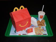 Happy Meal box 4 layers of 6in cake, in buttercream, panels of dried out fondant I got the tray from Michaels and printed the tray liner from the internet, then covered it with contact paper. cup and straw are fondant used a paper cup for the right shape. chicken nugget box is fondant (I dried it over a real nugget box). The fry holder is also fondant (dried over some cardstock). The chicken nuggets are cake balls!