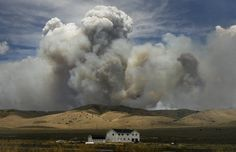 (Scott Sommerdorf  |  The Salt Lake Tribune)               A farmhouse just off Hwy 132 near Fountain Green is dwarfed by a huge cloud of smoke caused by the brush fire near there, Sunday, June 24, 2012.
