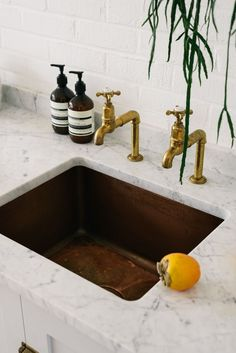 Aged copper sinks and aged brass taps go so beautifully with Carrara marble