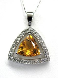 Ladies 14kt white gold gemstone and diamond pendant. Mounted in pendant is a trillion cut citrine and 27 brilliant round cut diamonds weighing approximately .38ct. Pendant comes with a 18 inch white gold chain.