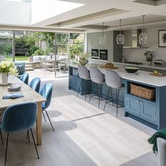 A row of floor-to-ceiling windows and a large skylight work together in this kitchen-diner to create a bright and airy space. Teal cabinetry and upholstery add a pop of contemporary colour. The row of three glass pendant lampshades complete the modern look.
