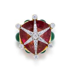 Top view of a pink tourmaline, emerald and diamond ring by Tony Duquette;centering a shield-shaped pink tourmaline surmounted by round brilliant-cut diamond starburst detail within an openwork mount accentuated by oval cabochon emeralds; pink tourmaline weighing approximately: 51.85 carats, mounted in 18kt yellow gold.  Sold at auction for 10,625 USD.