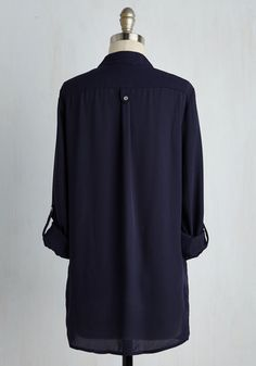 When you want a work wardrobe that's subtle, stylish, and a little bit romantic, make this breezy, navy blue blouse your business! Everyone will want to copy the modestly marvelous style of this top - its gathered shoulders, low collar, and iridescent buttons always garner a good reception.Tickled by this cute, ModClot-exclusive tunic? Check out this dashing design in a host of other haute hues!